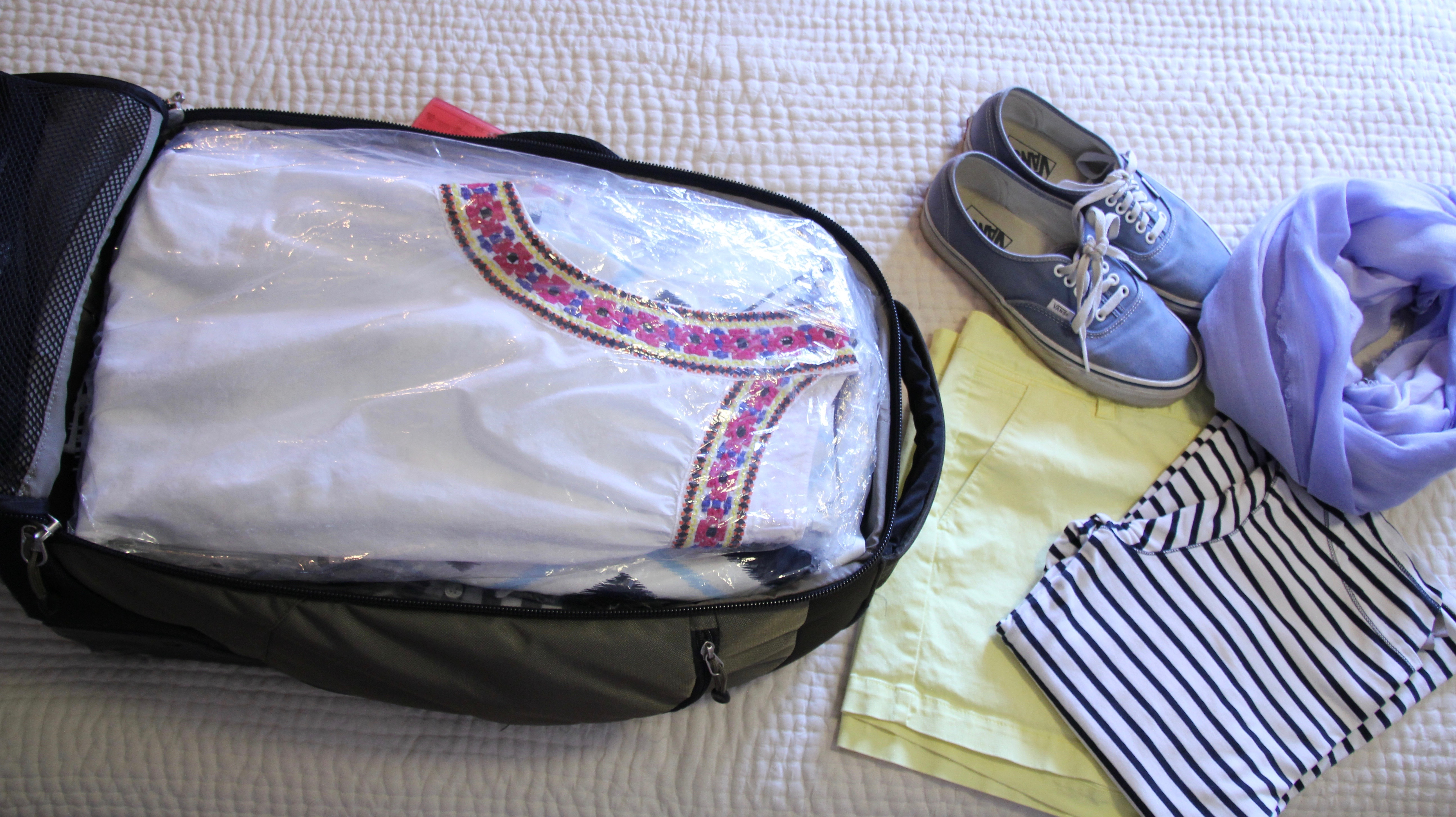 packed suitcase and travel outfit
